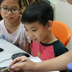 [ADAM KHOO LEARNING CENTRE] Participants of the inaugural Young Coders Bootcamp 2017 having a fun time revising what they had learnt during the 2